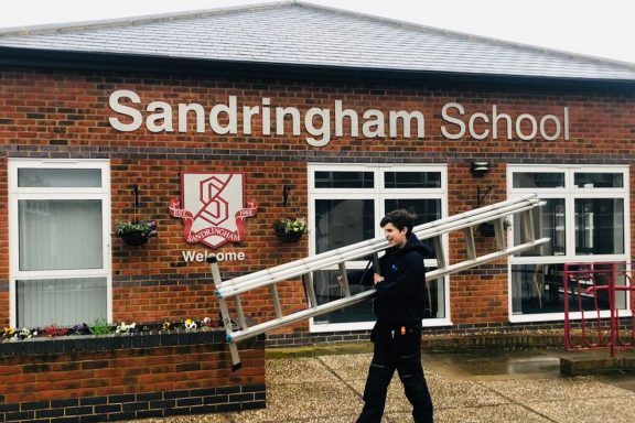 Sandringham school front with Amthal employee posing with a ladder